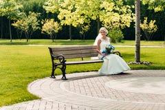 Junge blonde Braut, die auf einer Bank in einem exotischen Park sitzt Stockfotografie