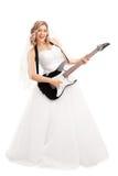 Junge blonde Braut, die E-Gitarre spielt Lizenzfreie Stockfotos