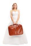 Junge blonde Braut, die eine braune Tasche hält Stockbild