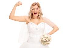 Junge blonde Braut, die ihr Bizeps biegt Stockfotos