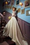 Junge blonde Braut im Hochzeitskleid Stockfotos