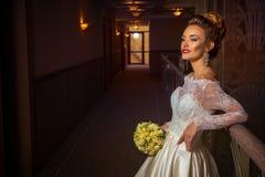 Junge blonde Braut im Hochzeitskleid mit Rosen in ihren Händen Lizenzfreies Stockfoto