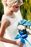 Junge blonde Braut mit einem Blumenstrauß von Blumen in ihren Händen Stockfotografie