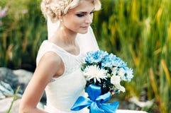 Junge blonde Braut mit einem Blumenstrauß von Blumen in ihren Händen Stockbilder