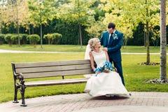 Junge blonde Braut sitzt auf einer Bank nahe bei dem Bräutigam in einem exotischen Park Stockfoto