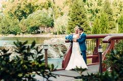 Junge blonde Braut steht nahe bei dem Bräutigam in einem exotischen Park Lizenzfreies Stockfoto