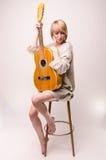 Junge blonde Dame in der grauen Strickjacke, die auf Stuhl sitzt und Akustikgitarre spielt Stockfotos