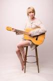 Junge blonde Dame in der grauen Strickjacke, die auf Stuhl sitzt und Akustikgitarre spielt Stockbilder