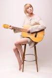 Junge blonde Dame in der grauen Strickjacke, die auf Stuhl sitzt und Akustikgitarre spielt Lizenzfreie Stockfotografie