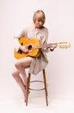 Junge blonde Dame in der grauen Strickjacke, die auf Stuhl sitzt und Akustikgitarre spielt Stockfotografie