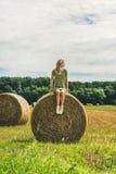Junge blonde Dame, die auf Heuschober sitzt und weg, Ungarn schaut Lizenzfreies Stockfoto