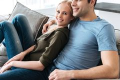 Junge blonde Dame, die Kamera beim Sitzen mit ihrem Mann schaut Stockfotos