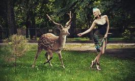 Junge blonde Dame, die mit Rotwild läuft Stockfoto