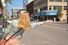 Junge blonde Dame ruft ein Taxi auf der Straße Stockbilder