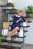 Junge blonde elegante Frau, die ihre Einkaufstaschen auspackt Lizenzfreie Stockfotografie