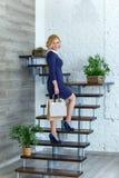 Junge blonde elegante Frau mit Einkaufstaschen auf der Treppe Lizenzfreies Stockbild