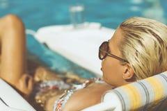 Junge blonde Entspannung in einem Pool Lizenzfreie Stockfotos