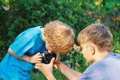 Junge blonde Fotografen mit einer Kamera draußen Lizenzfreies Stockbild