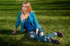 Junge blonde Frau auf dem Gras Stockfoto