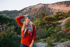 Junge blonde Frau auf dem Hintergrund des Berges und des Waldes Stockbilder
