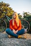 Junge blonde Frau auf dem Hintergrund des Fahrrades und des Waldes Stockbild