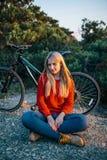 Junge blonde Frau auf dem Hintergrund des Fahrrades und des Waldes Stockfotografie