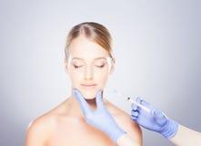 Junge blonde Frau auf einem Gesichtseinspritzungsverfahren Stockfotografie