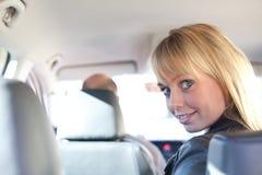 Junge blonde Frau auf einem Rücksitze eines Autos Lizenzfreies Stockbild