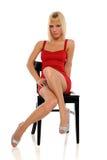 Junge blonde Frau auf einem schwarzen Stuhl Lizenzfreie Stockfotos