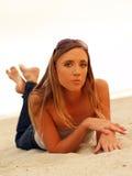 Junge blonde Frau auf Sandjeanssonnenbrillen Stockfoto