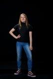 Junge blonde Frau auf schwarzem Hintergrund Lizenzfreie Stockfotos