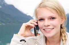 Junge blonde Frau aufgerufen mit ihrem Smartphone Stockfotos