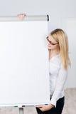 Junge blonde Frau betrachtet Flip Chart Lizenzfreie Stockbilder