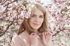 Junge blonde Frau in blühendem Kirschblüte-Garten Lizenzfreie Stockfotos