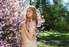 Junge blonde Frau in blühendem Kirschblüte-Garten Stockfotografie
