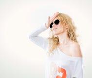 Junge blonde Frau in den dunklen Gläsern und in einer weißen Strickjacke Stockbild