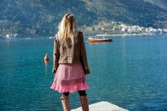Junge blonde Frau in den rosa Gläsern und im Kleid nahe dem Meer auf einer SU Stockfotos