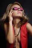 Junge blonde Frau in den rosafarbenen Gläsern Stockfotografie