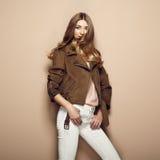 Junge blonde Frau in der braunen Jacke Stockfotografie