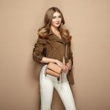Junge blonde Frau in der braunen Jacke Stockbilder
