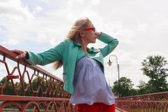 Junge blonde Frau in der Lederjacke und in Gläsern, die auf der roten Brücke untersucht den Himmel aufwerfen Stockfotos