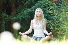 Junge blonde Frau in der Lotoshaltung Lizenzfreies Stockfoto