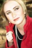 Junge blonde Frau in der roten Jacke Lizenzfreie Stockfotos