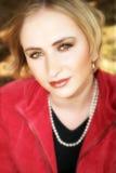 Junge blonde Frau in der roten Jacke Stockfotografie