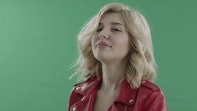 Junge blonde Frau in der roten Jacke, die gegen grünen Schirm nett ist stock video footage