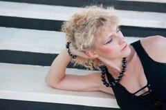 Junge blonde Frau in der schwarzen Lüge auf dem white&black Hintergrund Stockfoto