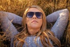 Junge blonde Frau in der Sonnenbrille, die im goldenen Gras liegt Stockbild