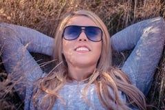 Junge blonde Frau in der Sonnenbrille, die im goldenen Gras liegt Stockfotografie