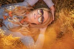 Junge blonde Frau in der Sonnenbrille, die im goldenen Gras liegt Lizenzfreie Stockbilder