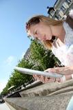 Junge blonde Frau in der Stadt unter Verwendung der Tablette Stockbilder
